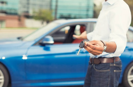 A man holding out keys and gesturing to a blue car.
