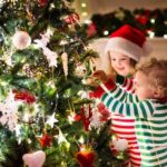 Two children decorating a Christmas tree.