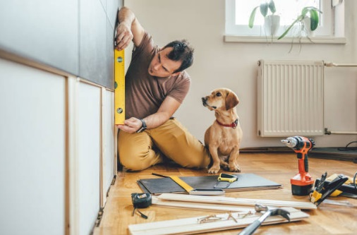 A man remodeling his home. His dog looks on with interest.
